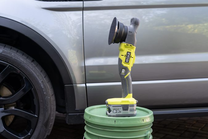 Ryobi One+ Dual Action Polisher stood next to clean car